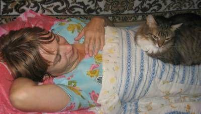 Кішка спить на жінці
