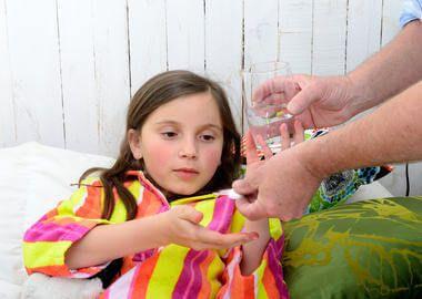 Дівчинка приймає таблетку від горла