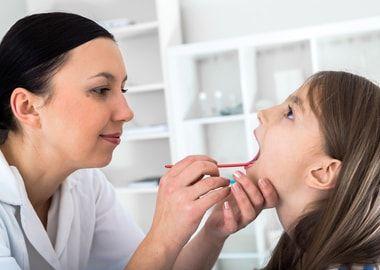 Лікар діагностує гнійний фарингіт у дівчинки
