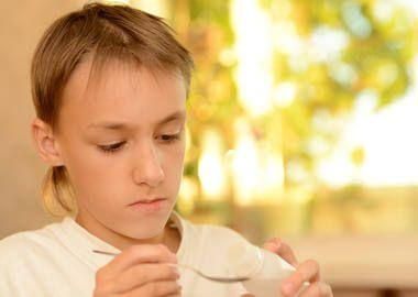 Дитина приймає ліки від болю в горлі при фарингіті