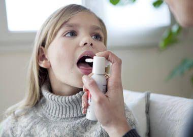 Дитина зрошує горло спреєм від фарингіту
